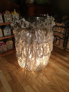 Doily project - one gallon Mason jar, great, great grandma's hand made doily, wired around the top - garnished with white satin ribbon.  A sting of silver star garland and a strand of white twinkle lights - simply beautiful!