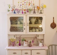 pink cupboard accented with various little vases of flowers