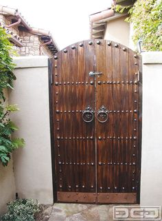 Rustic decorative hardware such as Spanish iron clavos, iron slide locks and hammered copper kick plates such as the ones found on this custom passage gate are elemental features that cross the borders of architectural design in such a manner that a simple plank arched gate like this suddenly becomes a heavily ornate art piece. …