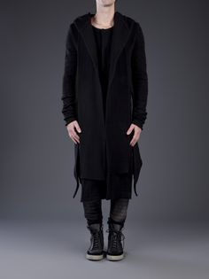 Wraith coat in black from ØDD. This heavy wool coat features a hooded shawl collar with ribbed stitching, a round neck, and a concealed snap button closure in the front. Has long silk knit sleeves, side seam pockets, and tonal black suede panels at the sides. Includes a mid-length hem and a single interior pocket.