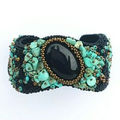 This bracelet is a V-shaped mix of black, turquoise and gold colours.  Focal are 3 black onyx cabochon, surrounded with turquoise gemstone chips and