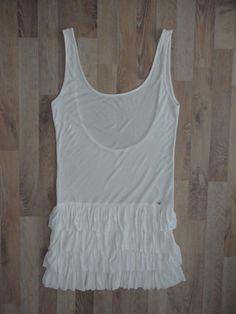 Vestido de algodón blanco, escote redondo, espalda descubierta y pollera con capas de volados #ossira #ModaSustentable. Compra esta prenda en www.saveweb.com.ar!