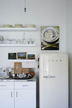 Open shelves in the galley kitchen hold cream china, pressed glass, Britain cast metal figures and kitchenalia.  Above a retro-inspired Smeg refrigerator is 'Contemplation' (2007) by Justin Van den Berg.  Pendant light globes were specially chromed.