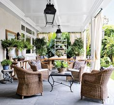 On the main terrace of fashion executives Patrick Wade and Dave DeMattei's home in Beverly Hills, California, wicker club chairs are arranged around a vintage French Art Deco iron table.
