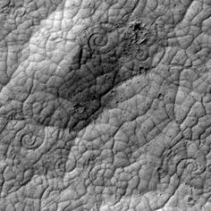 Image from the HiRISE camera aboard the Mars Reconnaissance Orbiter reveal curious spiral shapes on the surface of Mars.