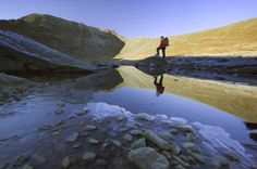 A hiker is reflected in the icy waters of Red Tarn with Helvellyn in the background, Cumbria, England, England, UK