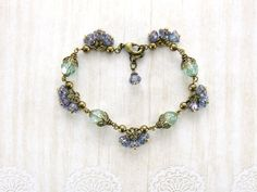Sage and lavender nature inspired floral bracelet with antiqued brass, Czech glass flowers and Swarovski crystal pearls. Vintage style wedding and gift ideas by ArdentHearts