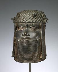 """The sculpture stands nearly twelve inches high and dates between 1550 and 1650, the so-called """"middle period"""" of Benin art, which many consider the high point of Benin artistic production. The Benin culture is known for creating superb bronze sculptures to honor its Obas (or kings). In this case, the Oba is shown wearing a hat and a multi-strand coral-bead necklace, with another coral bead on his forehead.  This sculpture is now owned by The  Minneapolis Institute of Arts"""