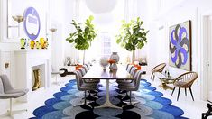 The 11 Greatest Lessons We Learned From Jonathan Adler // eclectic modern dining room, blue rug, tulip chairs, brass boot, mantle, fireplace, fiddle leaf fig