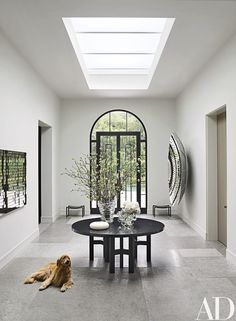 In the central hall, the skylight brightens an Ado Chale table from Hedge (the San Francisco gallery co-owned by Volpe, and the source of many of the house's furnishings); the work at left is by Random International, and at right is a piece by Anish Kapoor. The owner's golden retriever lies on a floor of limestone; the paint is by Benjamin Moore.