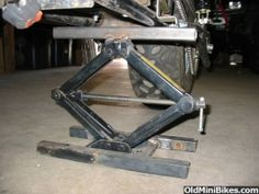 Homemade adjustable stand and motorcycle lift constructed by welding sections of square tubing to a scissor jack's lifting saddle and foot plate.