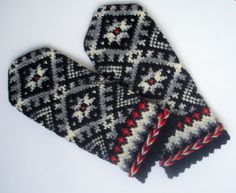 Hand knitted wool mittens Warm mittens Winter gloves White ornament gray background Christmas gift idea White grey black Latvian mittens