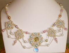 Feel like a queen in layers of lacy beads! At the heart of the necklace is a 14mm Luminous Green Swarovski crystal, surrounded by various shades of ivory, pastel glass pearls, and rose quartz beads. An aurora borealis coated crystal briolette gives the finishing touch of sparkle to the center bezel. The necklace is finished with a lead-free gold-plated pewter toggle clasp.  $80.00
