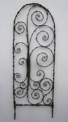 Barbed Wire Trellis Bristling With Spiky Spirals by thedustyraven Wire Crafts, Metal Crafts, Barbed Wire Art, Wire Trellis, Garden Structures, Outdoor Art, Shabby, Wire Work, Yard Art