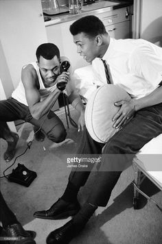 American photographer Howard Bingham (left) and his friend boxer Muhammad Ali (then known as Cassius Clay) make a telephone call, 1963. Ali holds a round throw-pillow between his knees.