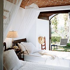 Light and Breezy  Mosquito netting is essential to open-air island bedrooms, but the flowy material has exotic appeal everywhere. Hang netting from a canopy bed frame like curtains or suspend it, hoop-style, from the ceiling.