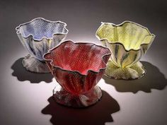 Curtis Benzle  He produces incredibly thin forms that glow like stained glass.  Hand built, often bowl-shaped, overlapping images formed from slabs taken frrom intricately patterned blocks of coloured porcelain.  Layering these, he creates vessels with different inside and outside patterns, that merge softly as light floods through the thin porcelain.  Draws viewer into an intimate reality with a vision that suggests a landscape but ultimately is more personal and colourful