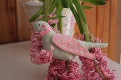 In liebevoller und aufwendiger Handarbeit genähter Vogel nach Tilda aus Baumwollstoff.  Der Halsschmuck besteht aus einem rosa Satinband und einer ros