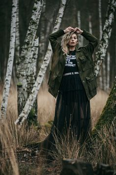 emotional fashion editorial in a birch forest   outfit style: dark, sad, grunge, edgy, goth, sexy   Vogue, black maxi skirt and military coat