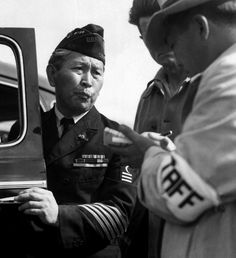 Dressed in uniform marking his service in the First World War, a veteran enters a relocation centre for Japanese-Americans bound for internment. Arcadia, California, 1942. Dorothea Lange