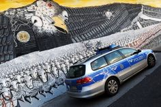 "A police car passes a mural painting featuring the emblematic US eagle with a badge that reads ""National Security Agency worldwide"" at the at the Ehrenfeld railway embankment in Cologne, western Germany on Thursday."
