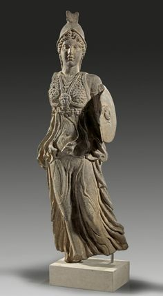 Basalt figure of Athena, 2nd - 3rd century A.D. The Goddess is holding a shield and dressed in a waving chiton pressed to her body by her vivid movement. A two-partite aegis is covering her chest. A pseudo-corinthian helmet protects her head.