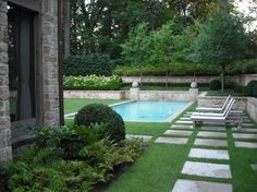 Grass, pavers, trees, stone half walls.