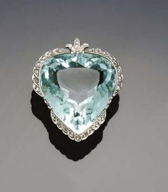 An early 20th century aquamarine and diamond brooch/pendant   the pear shaped mixed-cut aquamarine with rose-cut diamond edging, circa 1915, with later single-cut diamond trefoil pendant loop surmount.