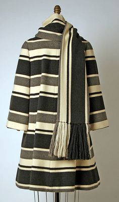 Balmain Haute Couture dress ensemble with matching striped pattern design coat jacket and long shawl drape from 1963-1967. White color dress with front pom pom tied in high neck, long sleeve shirt style top with black and grey stripe color mini a line skirt from designer Pierre Balmain. House of Balmain 1960 vintage fashion collection.