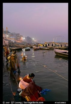 Women soaking clothes in the Ganges River at dawn. Varanasi, Uttar Pradesh, India