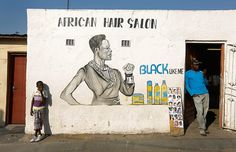 People stand outside the African Hair Salon in the late afternoon sunlight. Townships like Alex, Diepsloot and Soweto were built outside the main white areas as a cornerstone of South Africa's apartheid policy.