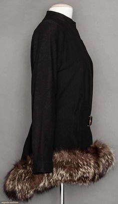 "Black wool, H length, fitted through W, band collar w/ 1 hook & eye, open F to large black & gold buckle at W, fox fur hem trim, white silk label w/ ""Madeliene Vionnet"" in dark green script,"