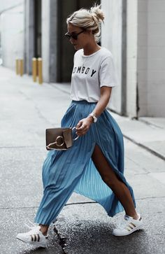 white and gold adidas, blue pleated maxi skirt with side slit, white t shirt, sunglasses and top knot