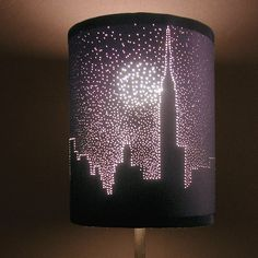 Dark lamp shade, use push pins to make stars and city outline.