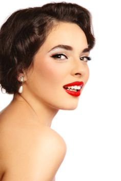 Looking for a short vintage style hairdo that is easy care?    This look is classic 50's style starting with a pixie cut that has a side part with the ends curled under toward the face on one side and the bangs gently swoop up and over to the other side. The brunette color matches her brown eyes and the red lipstick completes the look.  More on 1950's Short Hairstyle