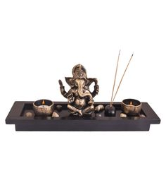 A beautiful and divine piece; this is a perfect addition to your home this season. It is a Ganesha statue placed on a rectangular tray with Antique Gold finish. Its fanked with two round inlay tea light holders (tea lights included) and an agarbati stand in the form of black stone. More stones enhance its beauty.