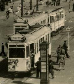 """1941 , Przystanek tramwajowy na Königsplatz. Rejsowy LH Standard na linii 25 jedzie w kierunku """"Ofener Str"""", z drugiej strony nadjeżdża dwuwagonowa 1 w kierunku """"Flughafen"""". Na przystanku zatrzymywały się (kiepsko widać) 1, 3, 6, 21 i 25. Jest to fragment widokówki. Jeśli to nie przeszkadzałoby w odbiorze użytkowników FP, to mam w zanadrzu więcej takiego typu powiększeń. Nie wszystkie widokówki sie nadają, ale jest sporo, z których można wycisnąć taką tramwajową/architektoniczną rodzynkę."""