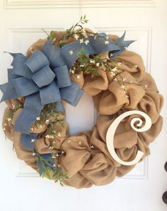 This is a beautiful burlap wreath measuring approximately 24. High quality tight weave burlap is base of wreath. Left side is adorned with little white flowers and simple greenery topped off with a denim look bow. Initial of your choice on the right. Initial can be painted your choice of color and is sprayed with acrylic for protection. Initial will be cream as pictured unless you specify otherwise. Place wreath in well protected area if using outdoors. If you like this wreath but would like…