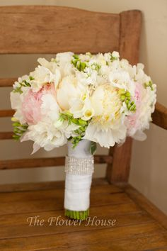 For Shanna's bouquet we wanted to make sure that it had the feminine elements while still keeping with her rustic feeling. We created the shape of her bouquet using fluffy Peonies in white and soft pink. To create the rustic feeling that this bouquet has, we used lighter flowers, which tend to have more movement. The Freesia and the Sweet Peas were able to bring in some green accents which gave depth and texture to the bouquet while still keeping a soft feeling.