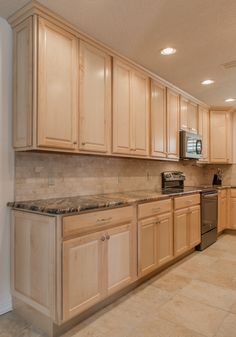 Merillat Classic 'Seneca Ridge' maple cabinetry with all the extras...full width roll out trays & a pull-down cookbook rack. Exotic Magna Gold granite countertops & a tumbled/unfilled marble backsplash.