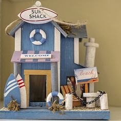 A blue figurine depicted an old-fashioned surf shack complete with miniature surf boards. Putz Houses, Fairy Houses, Diy Popsicle Stick Crafts, Cat Castle, Birdhouse Craft, Fishing Shack, Beach Cabana, Basket Crafts, Bird Houses Painted
