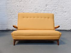 This sofa was manufactured in 1950. It is made from teak and afromosia with a mustard wood tweed upholstery.