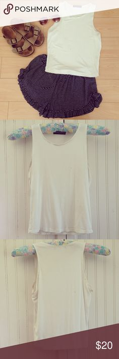 Brandy Melville White High Neck Tank This white tank by Brandy Melville is a closet staple. It's a super soft crop top that goes perfectly with a pair of Vodis or a cute skirt. The armpit area is slightly stained on both sides but it's hardly noticeable. Otherwise good condition. The neck line is pretty high so it provides nice coverage. Brandy Melville Tops Crop Tops