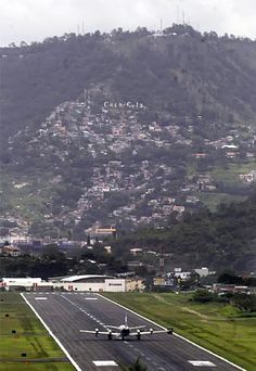 Toncontin International Airport, Honduras.  Yep, I've landed at this baby several times.  It's a heartstopper alright!  Super short runway with a mountain at the end.  Every person on d'plane is planting some heel on the floorboards.