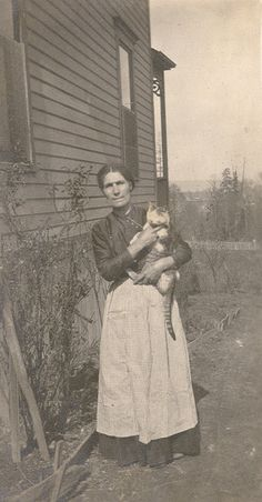 Country woman with cat. For a woman on an isolated farm or homestead on the prairie, a cat could be her close and affectionate companion.