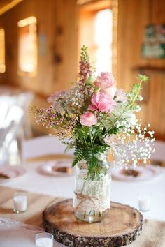 #Rustic and oh so pretty! Mason jars filled with snapdragons, roses, waxflower, fern & baby's breath, wrapped in lace and twine, and displayed on tree slices. {@jamieblow}