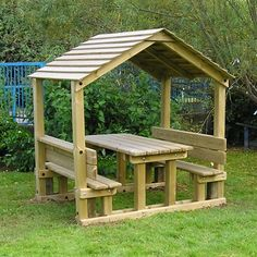Timber playground shelter - a wooden shelter for children with wooden benches and a table built in.