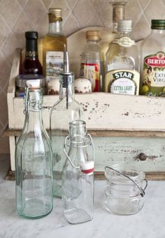 pretty idea to decant cooking staples into old bottles & corral them on a cool tray or container