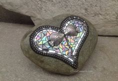 Pewter kissing fish are the focus for this Heart. Mosaic with mirror and a white iridescent glass outlined in multi - toned white and silver