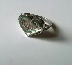 A gorgeous abalone shell ring. Thick solid hallmarked sterling silver. Beautiful iridescent rainbow colours that look more vibrant in real life. Ring size N, US size 7. The heart is a little over 1 and a half cm wide.